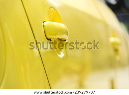 a shot of door handle of a yellow car - stock photo