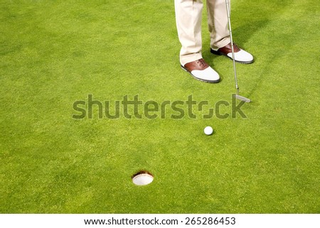 A shot of Golf player teeing up to hit ball - stock photo