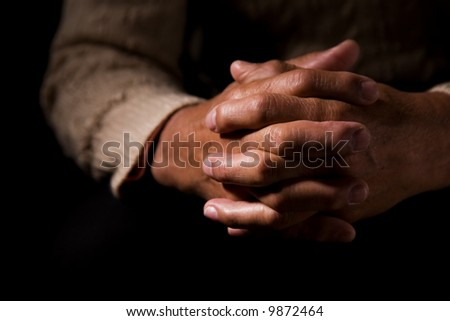 A shot of hands of an old man praying - stock photo