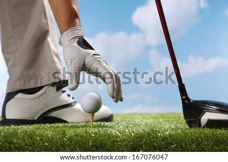 A shot of Placing golf ball on tee - stock photo