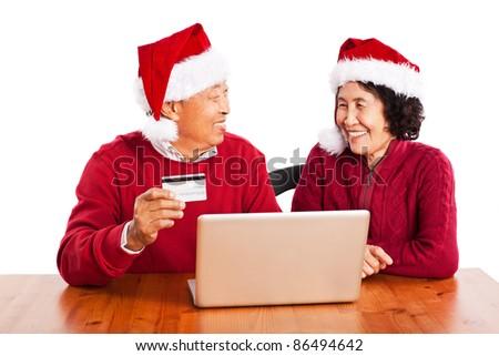A shot of senior Asian couple shopping online celebrating Christmas - stock photo