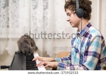 A shot of teenager boy playing piano  - stock photo