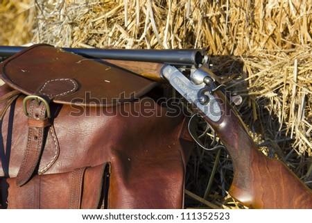 A shotgun and a backpack in the field to hunt - stock photo