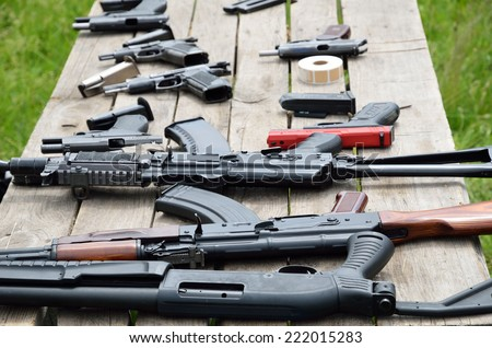 A shotgun, pistols and other firearm are laid out on the table outdoors. - stock photo