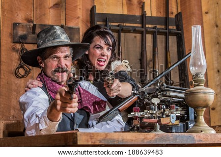 A Shouting Cowboy and Saloon Girl Point Their Weapons at You - stock photo