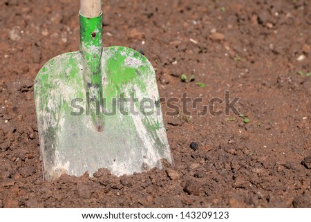 A shovel put in the soil in a garden - stock photo