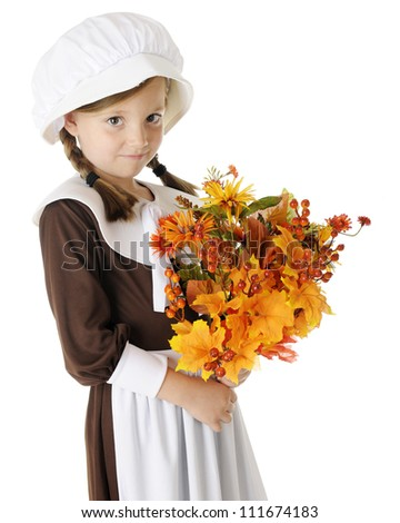"""A shy young elementary """"pilgrim"""" with a bouquet of autumn flowers, berries and leaves.  On a white background. - stock photo"""