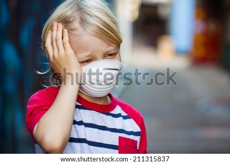 A sick and sad boy with a headache is wearing a protective face mask. - stock photo