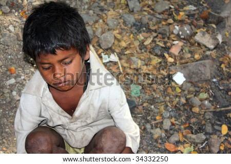 A sick beggar boy sitting hopelessly in his poverty conditions in India. - stock photo
