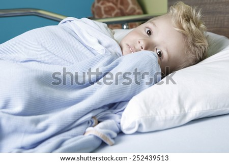 A sick little boy in a hospital bed - stock photo