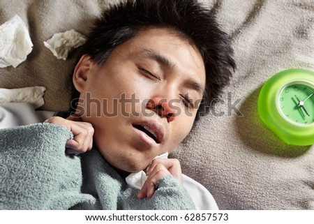 A sick male sleeping with clock near him - stock photo