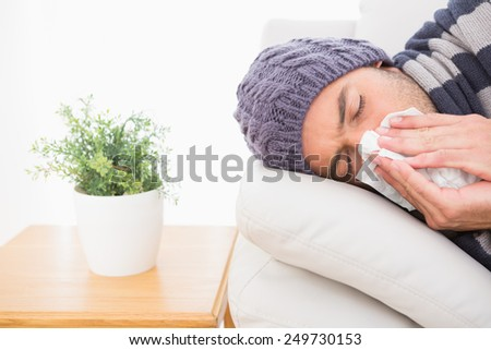 A sick man lying on the sofa in the living room - stock photo