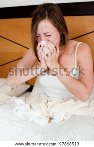 A sick young lady in bed, blowing her nose and with a lot of tissues lying in front of her. - stock photo