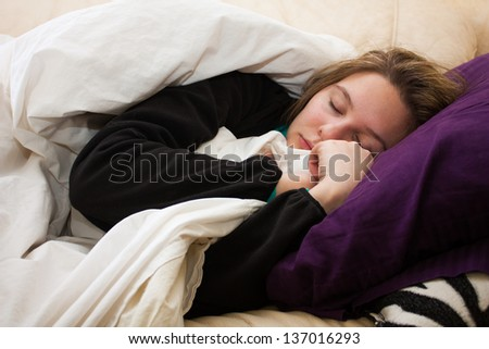 A sick young woman takes a nap on the couch, cuddled up with a blanket and - stock photo