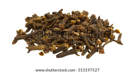 A side view of a pile of whole cloves on a wooden cutting board. - stock photo