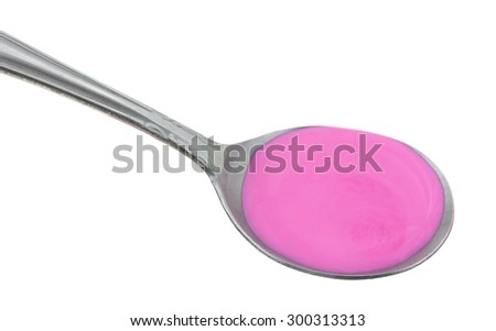 A side view of a silver spoonful of pink medicine for stomach relief. - stock photo