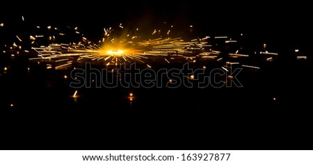A side view of a type of firework/cracker known as Chakra or Chakri rotating on the ground, during the Diwali festival celebrations in India  - stock photo