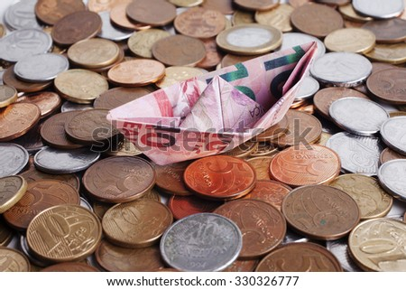 A side view of origami boat made of brazilian money with coins. - stock photo