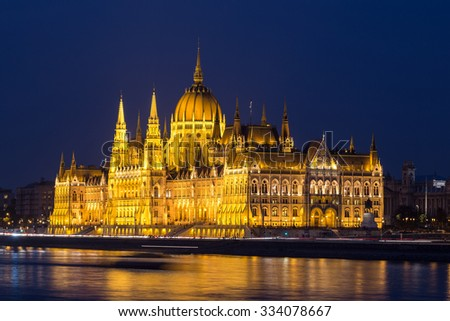 A side view of the Hungarian Parliament building along the Danube River at night with the building lit up and reflections in the water. There is space for text. - stock photo