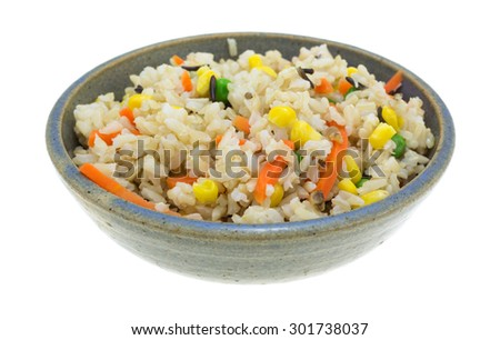A side view of wild rice and mixed vegetables in a gray bowl. - stock photo