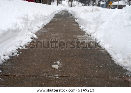 A sidewalk is cleared of snow. - stock photo