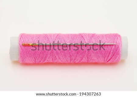 A sideways spool of pink thread and one needle stuck in the thread. - stock photo