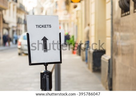 A sign and arrow directing to tickets in the streets of Barcelona - stock photo