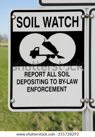 A sign asks local residence to report illegal soil dumping/Soil and Land Protection/A sign asks local residence to report illegal soil dumping.  - stock photo