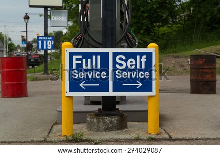 A sign at a gas station instructing people to go to the left for Full Service or the right for Self Service pumps - stock photo
