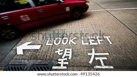 A sign at a street crossing in Hong Kong reminding tourists to look left before crossing - stock photo
