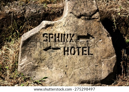 A sign carved into stone in the Drakensberg in South Africa indicates the way to the Sphinx and a Hotel. - stock photo