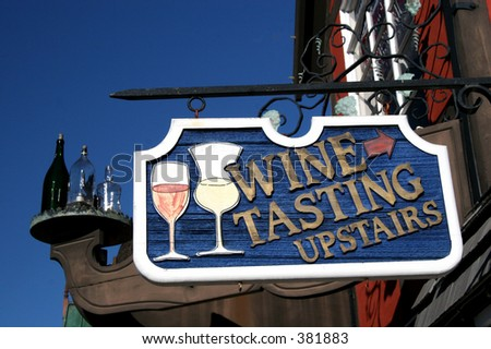 A sign directs customers upstairs for wine tasting. - stock photo