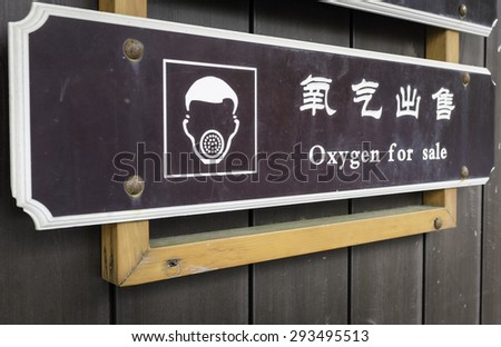 a sign informs about sale of oxygen for people having trouble breathing, on top of a mountain in China (selective focus on 'oxygen') - stock photo
