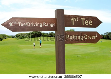 A sign on a golf course indicates the direction to the first tee, putting green, 19th tee and driving range at a country club. - stock photo