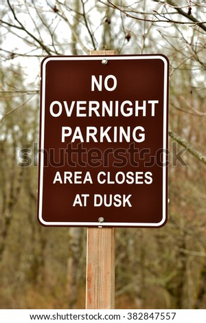 a sign on a wooden post stating that no overnight parking is permitted in the area - stock photo