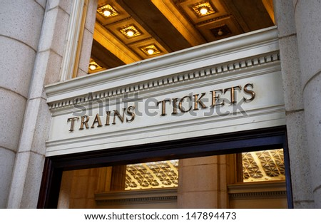 A sign pointing the way to train platforms and ticket windows inside a train station. - stock photo