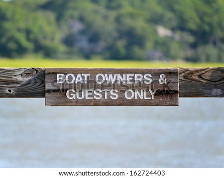A sign reading Boat Owners & Guests Only - stock photo