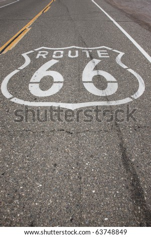 """A sign reading """"Route 66"""" is stenciled on the highway on a stretch of road that was once Route 66. - stock photo"""