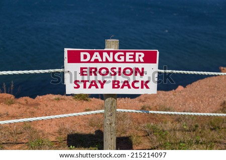A sign warning people of Erosion on a cliff - stock photo