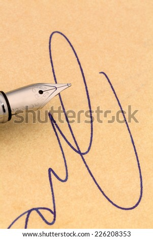 a signature and a fountain pen on yellow paper. symbol photo for contract testament and graphology - stock photo