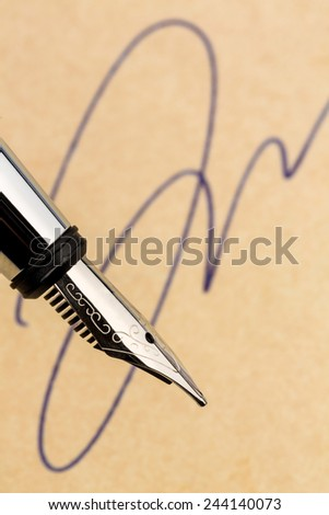 a signature and a fountain pen on yellow paper. symbolic photo for contract, testament and graphology - stock photo