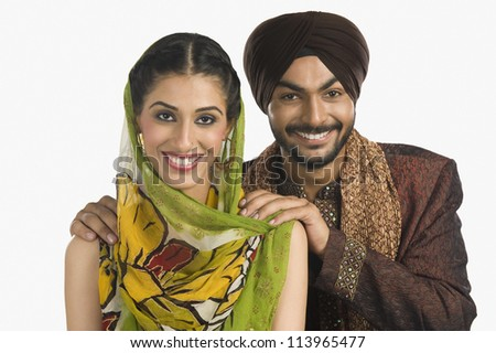 A Sikh couple smiling - stock photo