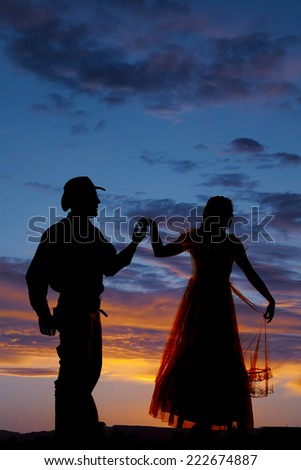 a silhouette cowboy holding on to his woman's hand. - stock photo