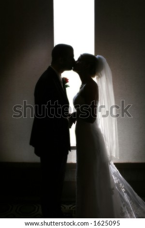 A silhouette of a bride and groom kissing in front of a narrow window. - stock photo