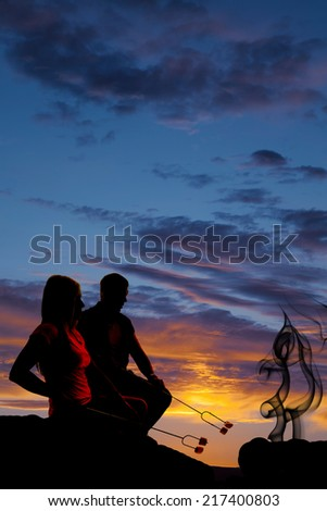 a silhouette of a couple in the outdoors roasting marshmallows. - stock photo
