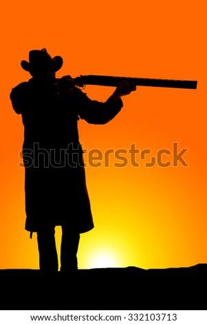 a silhouette of a cowboy aiming his shot gun ready to shoot. - stock photo