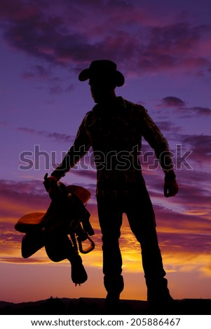 A silhouette of a cowboy in the outdoors, holding on to his saddle. - stock photo
