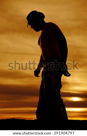 A silhouette of a cowboy in the outdoors, looking down. - stock photo