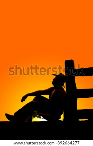 a silhouette of a cowboy sitting by a fence looking up deep in thought. - stock photo