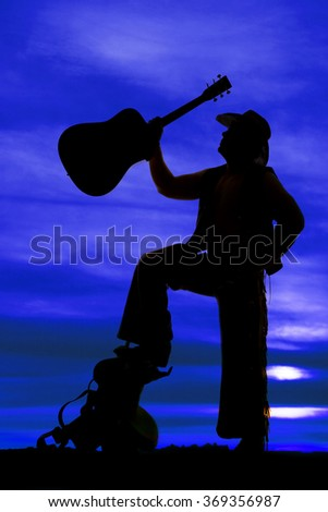 A silhouette of a cowboy standing up on a saddle with his guitar in the air. - stock photo
